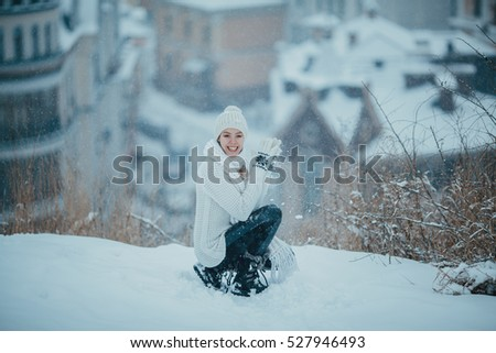 Happy young girl in white sweater enjoys the snow. Having fun in the snow. Joyful winter city.
