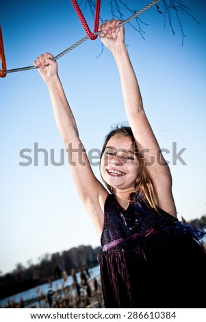 Happy young girl is hanging from the adventure playground and is really enjoying it. - stock photo