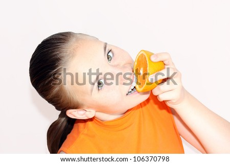 Happy young girl is posing with fresh oranges. More photos from this photoshoot  in my portfolio - stock photo