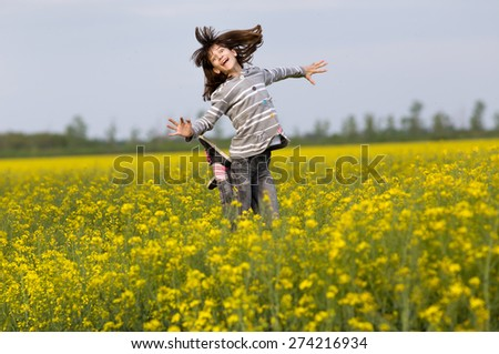 Happy young girl jumping in rapeseed field - stock photo