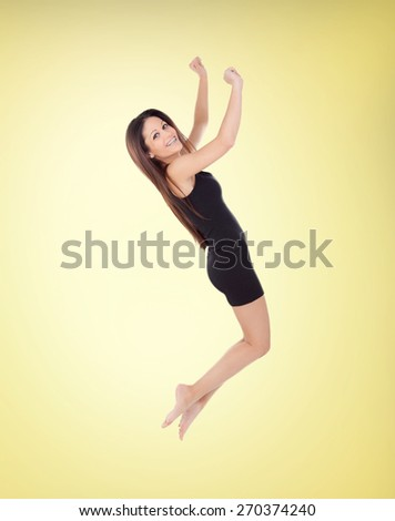 Happy young girl jumping with a short dress on a yellow background - stock photo