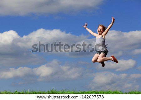 Happy young girl jumps in the meadow - stock photo