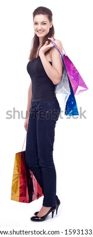 Happy young girl keeping shopping bags in her hands. Isolated on a white background. - stock photo