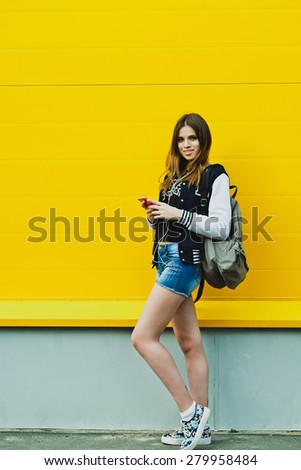 Happy young girl listening music  in headphones over yellowwall - stock photo