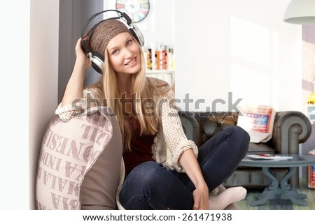 Happy young girl listening to music through headphones at home, smiling, looking at camera. - stock photo