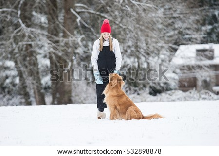 Happy young girl looking at her sitting golden retriever dog in
