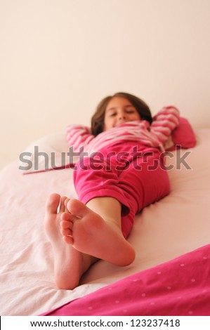 Happy Young Girl Lying On The Bed - stock photo