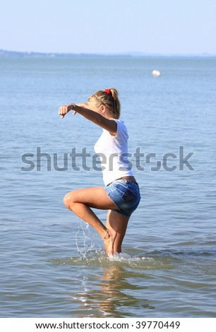 Happy young girl make tai-chi in the water