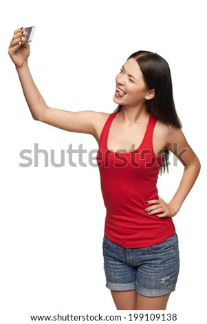 Happy young girl making funny face while taking pictures of herself through cellphone, over white background - stock photo
