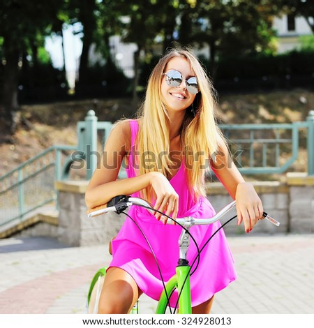 Happy young girl on a bicycle in summertime