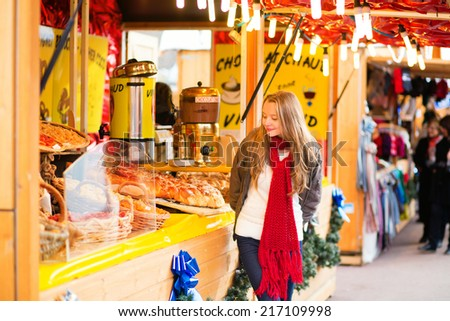 Happy young girl on a Parisian Christmas market, selecting Christmas treats - stock photo