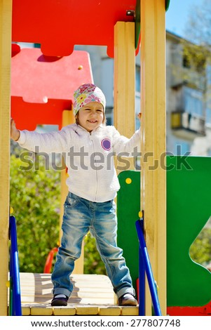 happy young girl on the playground in spring - stock photo