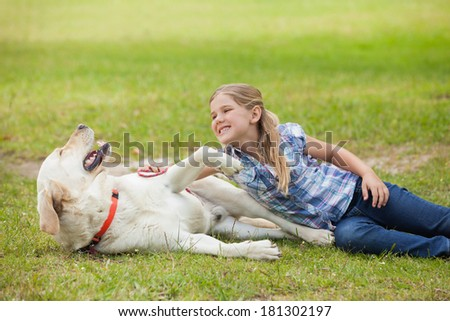 Happy young girl playing with pet dog at the park