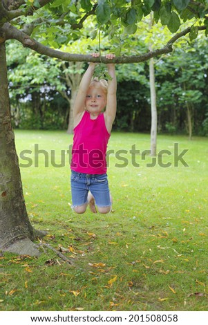 Happy young girl plays in the garden - stock photo