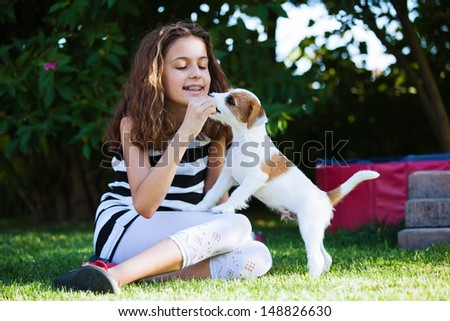 happy young girl plays with a cute Parson Russell Terrier puppy in the garden - stock photo