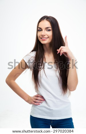 Happy young girl pointing finger up isolated on a white background. Looking at camera - stock photo