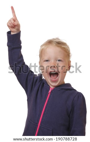 Happy young girl points finger in the air on white background