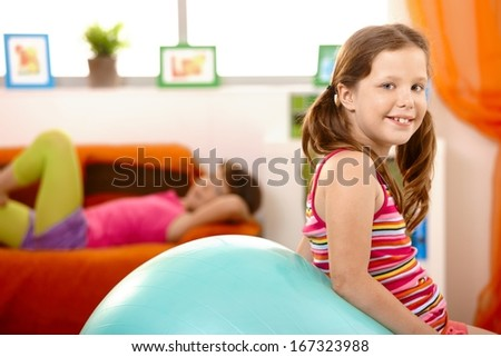 Happy young girl sitting on gym ball at home.