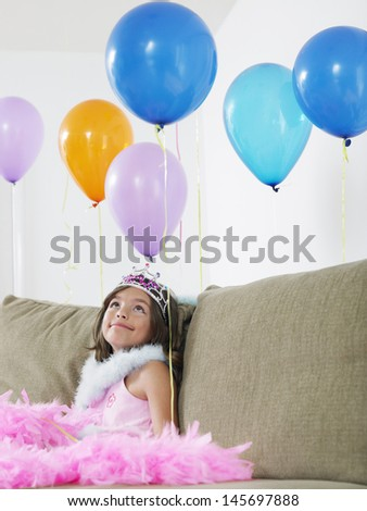 Happy young girl sitting on sofa and looking up at balloons - stock photo