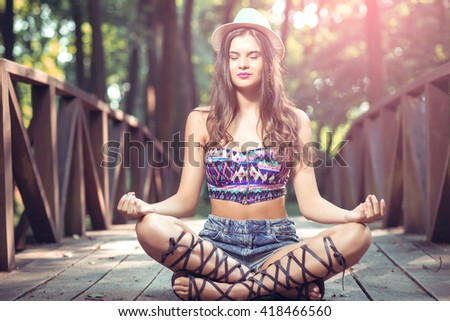Happy young girl sitting on wooden bridge and meditating. - stock photo