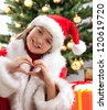 Happy young girl smiling near the Christmas tree. - stock photo