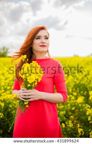 Happy young girl standing on spring field of yellow flowers, rape. Blue sunny sky. Concepts of success, happiness, harmony, health, ecology