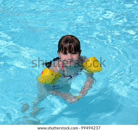Happy young girl swimming in tropical pool