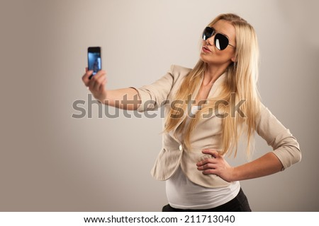 Happy young girl taking pictures of herself. young and attractive teenage girl with mobile phone - stock photo