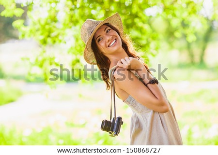 happy young girl wearing straw hat with vintage camera walking in the park and looking back, copy space from the left side
