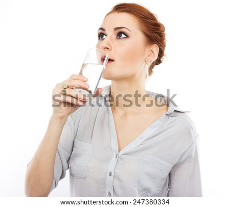 Happy young girl with a glass of water. A glass of water. Healthy life. Red-haired girl