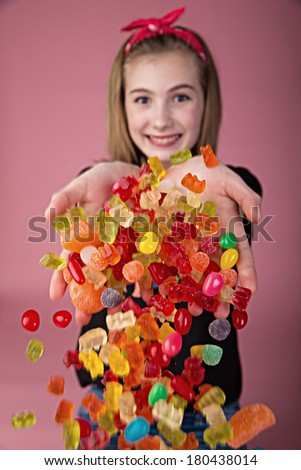 Happy young girl with a handful of colorful candy.