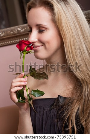 Happy young girl with a red rose - stock photo