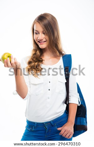 Happy young girl with backpack holding apple isolated on a white background