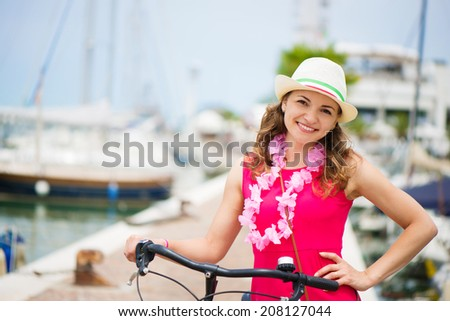 Happy young girl with bicycle in town - stock photo