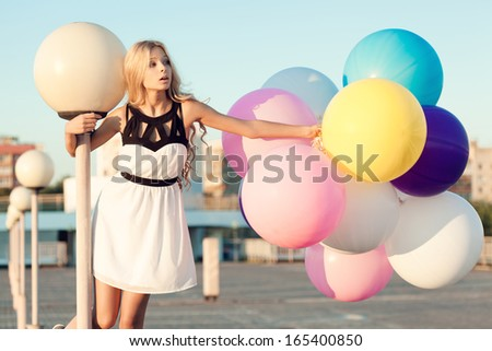 Happy young girl with big colorful latex balloons. Beauty Romantic Girl Outdoors. Woman on a lamppost on parking.