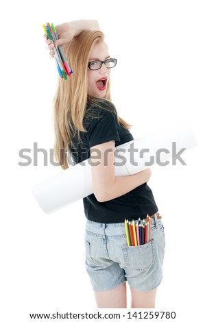 Happy young girl with  colored pencils, felt-tip  and white roll paper, wearing black t-shirt, denim shorts, glasses.  Creativity concept.