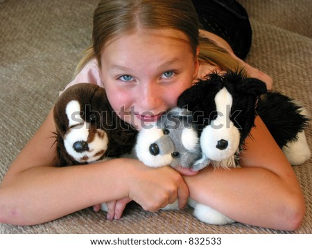 Happy young girl with her favorite plush toys.