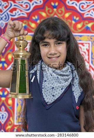 Happy Young Girl with Lantern Celebrating Ramadan over Ramadan Fabric - stock photo