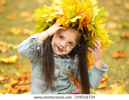 Happy young girl  yellow autumn wreath  in park