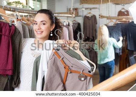Happy young girls choosing new clothes in shop