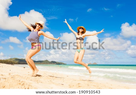 Happy young girls jumping at the beach. Summer beach fun.