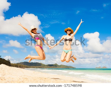 Happy young girls jumping on the beach. - stock photo