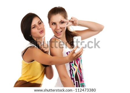 Happy young girls making funny face while taking pictures of themselves through cellphone - stock photo