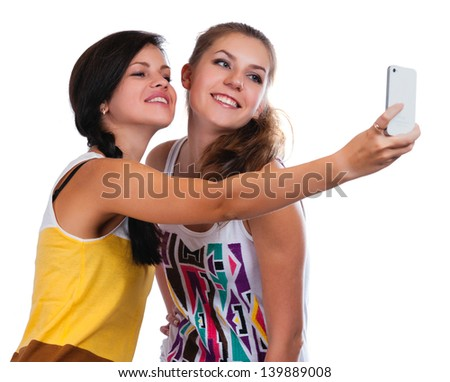 Happy young girls making funny face while taking pictures of themselves through cellphone