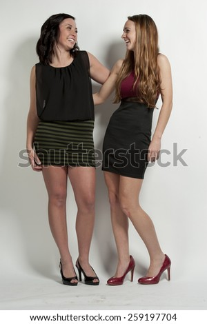 Happy young girls posing on a white background in a studio. - stock photo