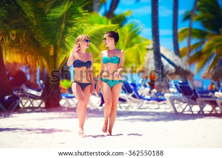 happy young girls walking on tropical beach, during summer vacation - stock photo