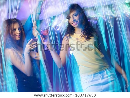 Happy young girls with drinks dancing at night club  - stock photo