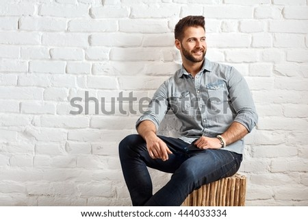 Happy young goodlooking caucasian man sitting at white brick wall, plenty of copyspace. - stock photo