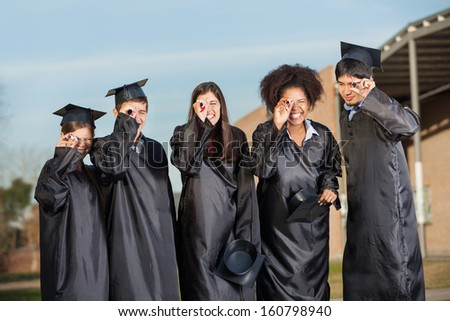 Happy young graduate students looking through diplomas on college campus - stock photo