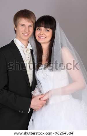 Happy young groom and bride hold hands in studio on gray background - stock photo